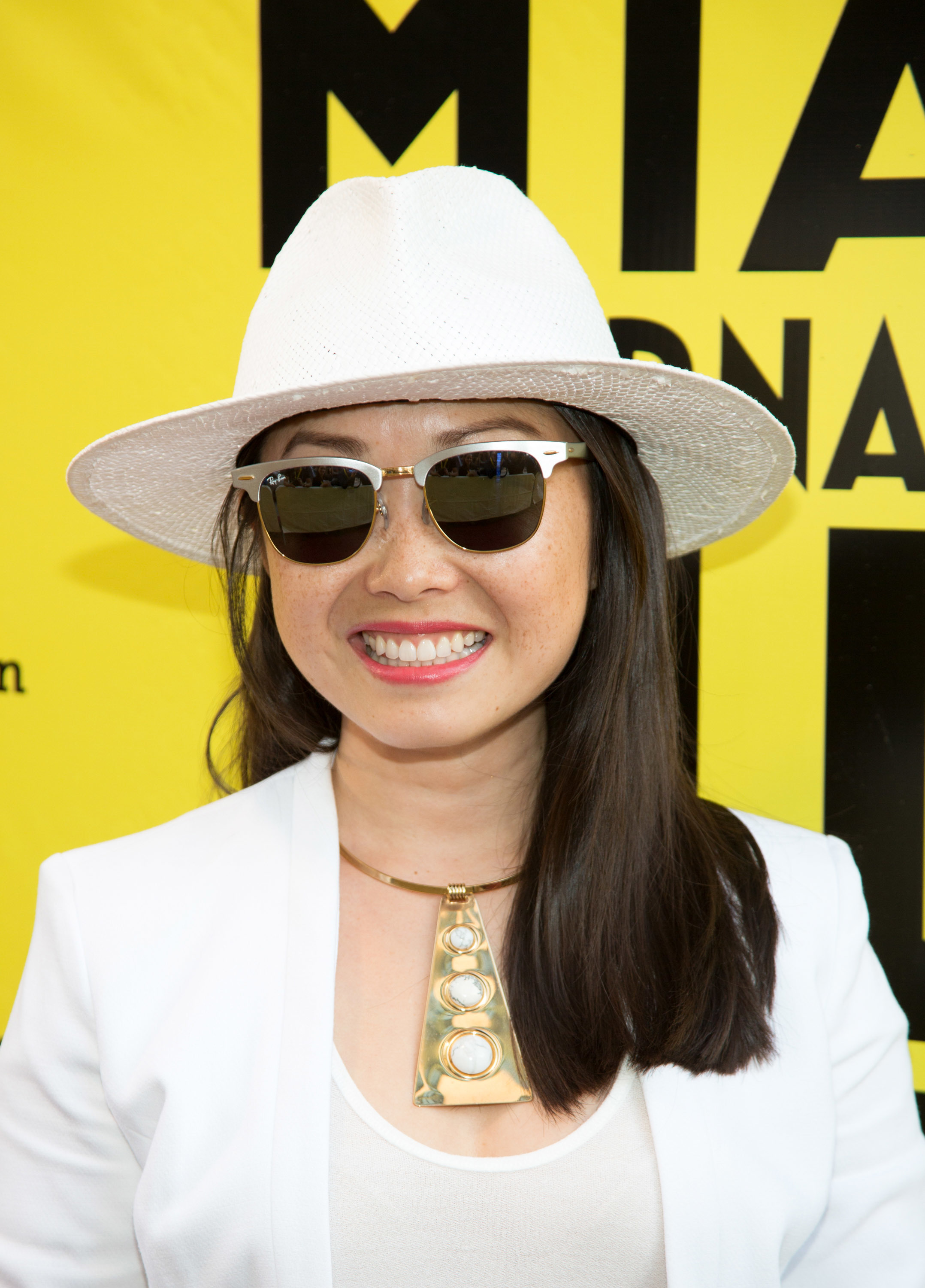 An adult in white clothes, white hat and sunglasses