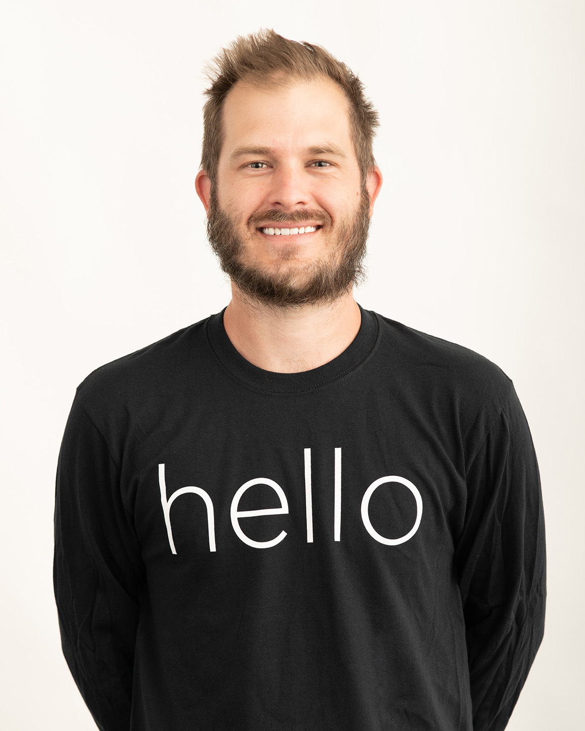 """Smiling person poses in a black T-shirt with white letter that reads """"hello"""""""