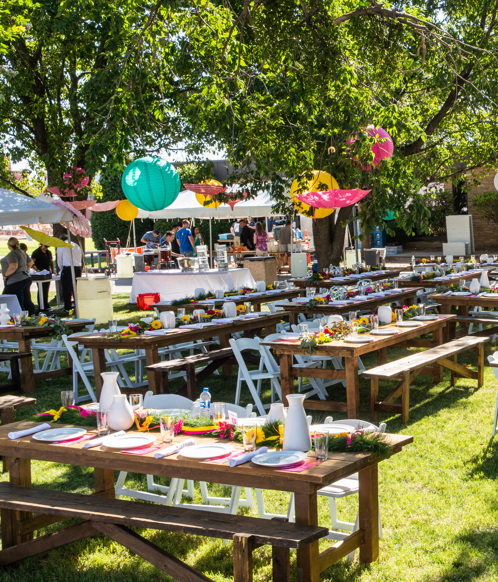 Farm-style tables covered in place setting stand under trees on a green lawn