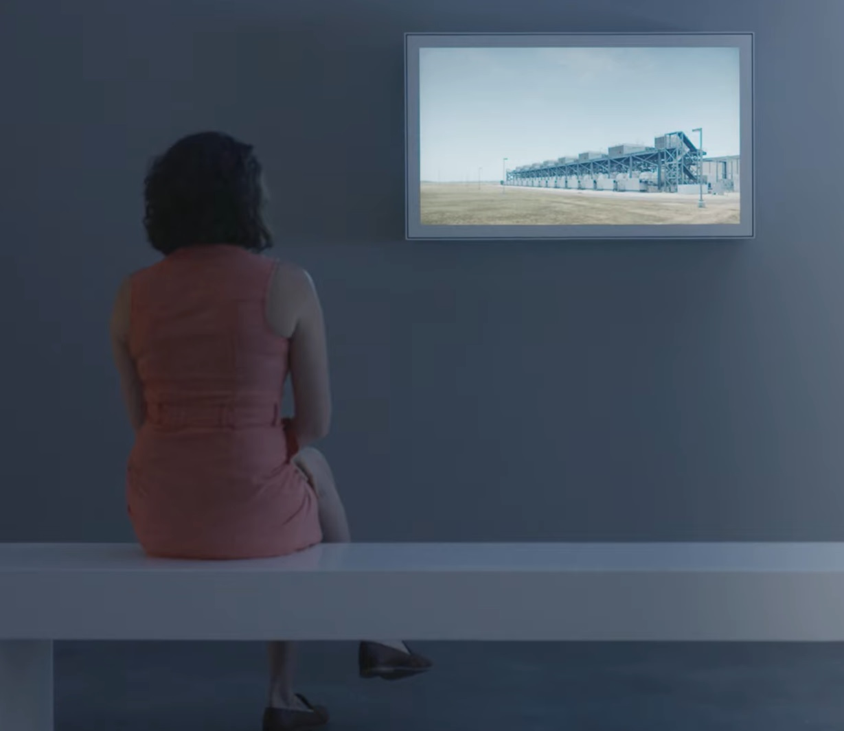 A person sits on a white bench in front of a video artwork