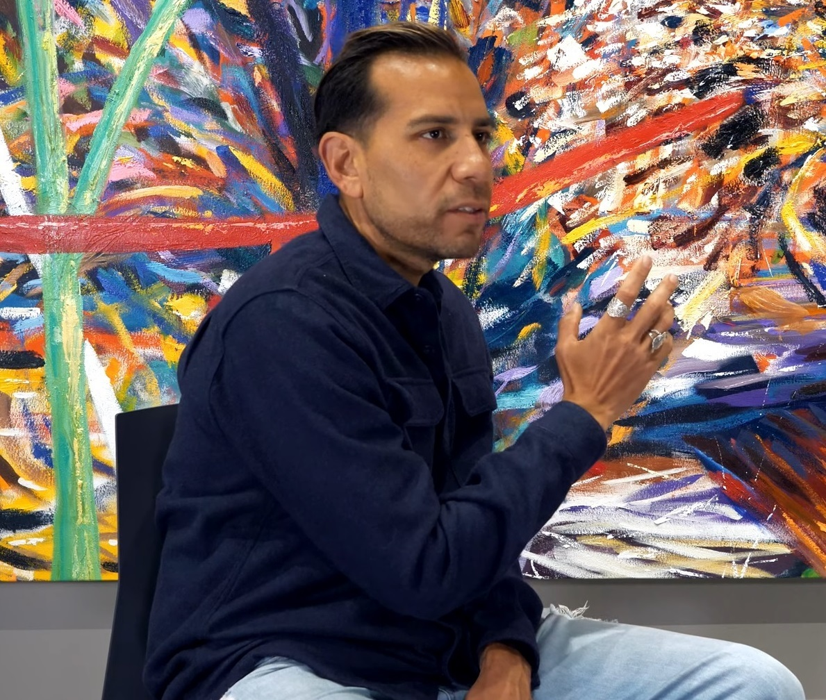 A seated person gestures with their right hand in front of an abstract landscape painting
