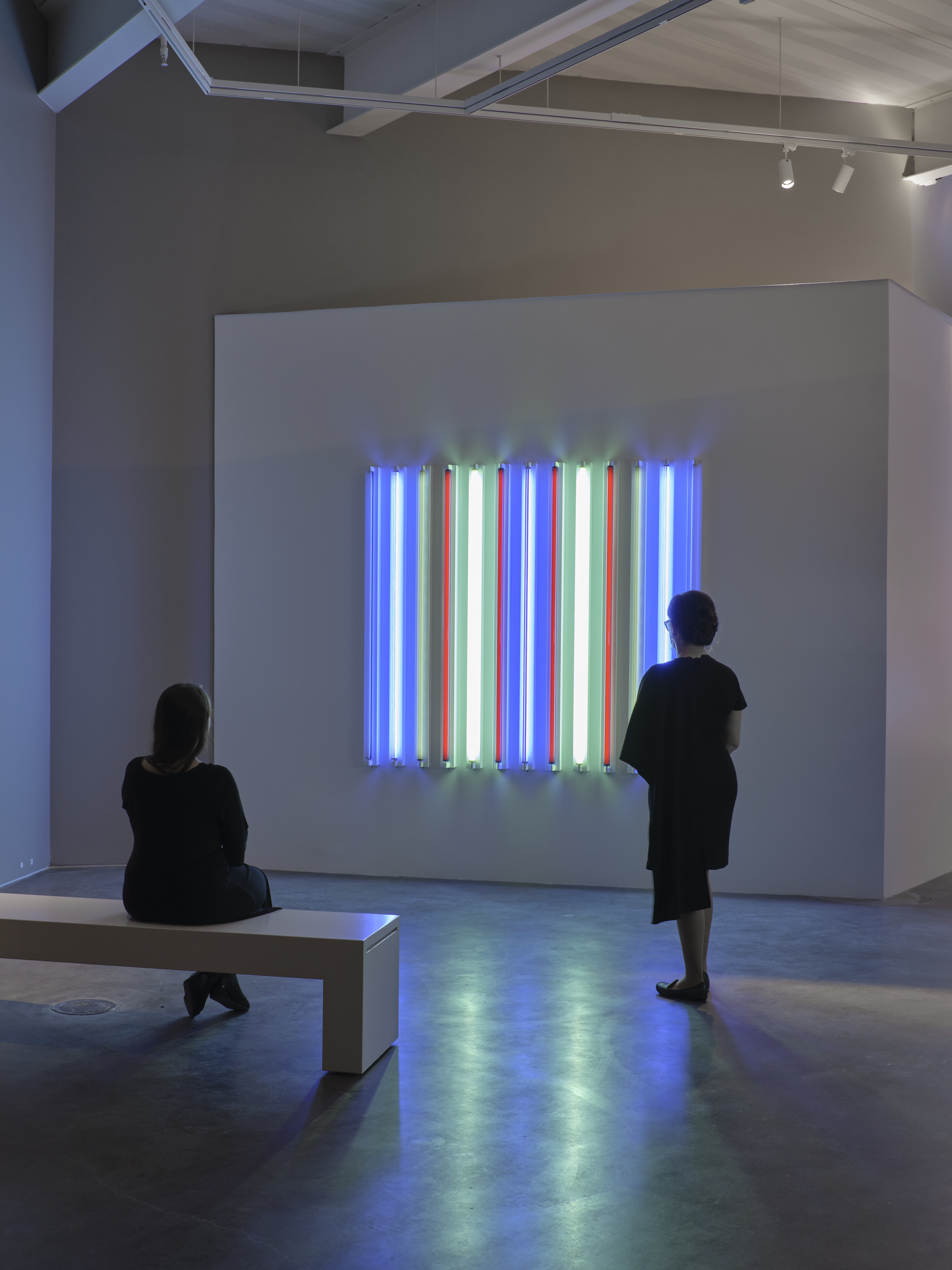 Two people, one seated on a bench and the other standing, observe a light sculpture in a contemporary art gallery