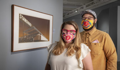 A young couple in masks stands in front of a screenprint of a sepia-toned gas station