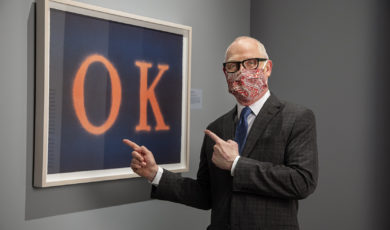 """A man wearing a suit and a mask points at  painting of the letters """"O"""" and """"K"""" in orange on a blue background"""