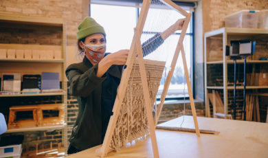 A person works on a hand loom in a studio space