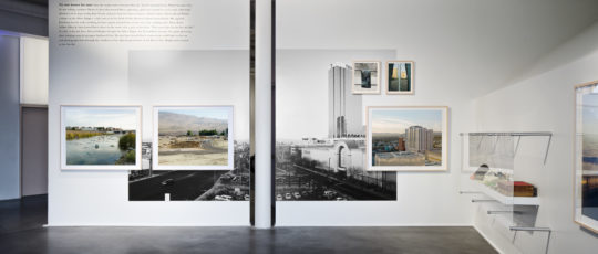 A photo of a wall in an art gallery featuring a block of text and a large black-and-white photo in vinyl plus framed photos atop it and a set of objects on a shelf