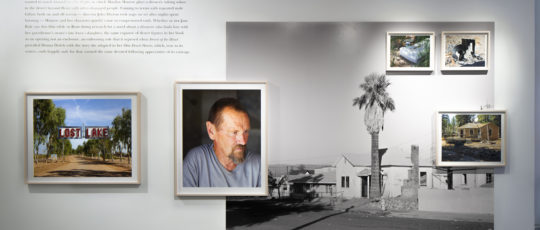 A photo of a wall in an art gallery featuring a block of text and a large black-and-white photo in vinyl plus framed photos atop it