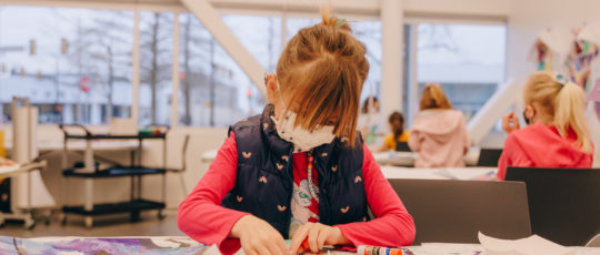A young girl in a mask and a vest works on an art project in a studio