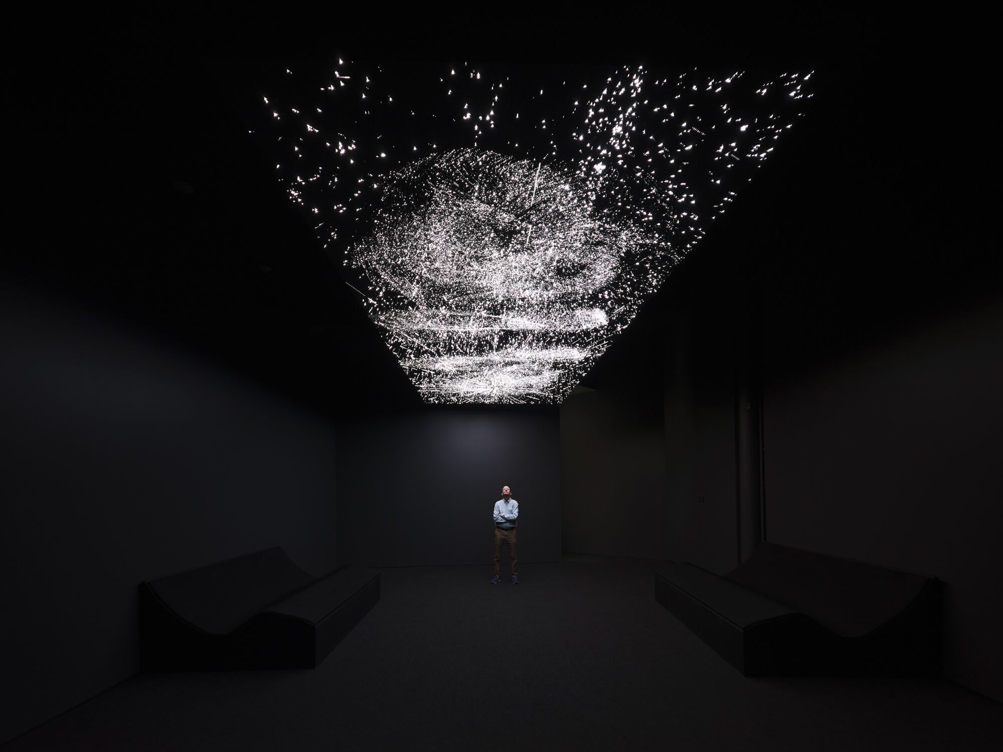 A person stands alone in a dark room, beneath a digital rendering of a starry sky