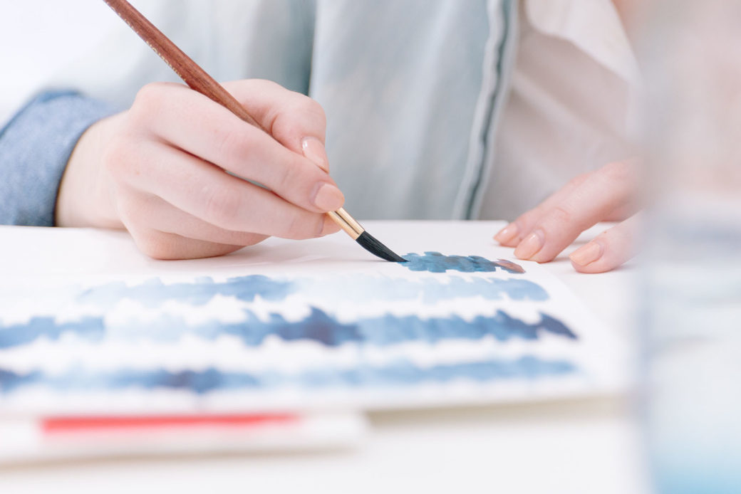 A detail photo of a pair of hands working on a watercolor painting