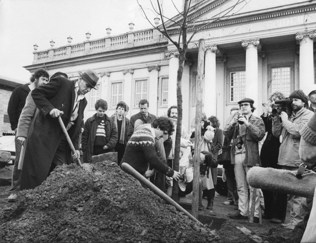 A black-and-white archive photo of a group planting a tree