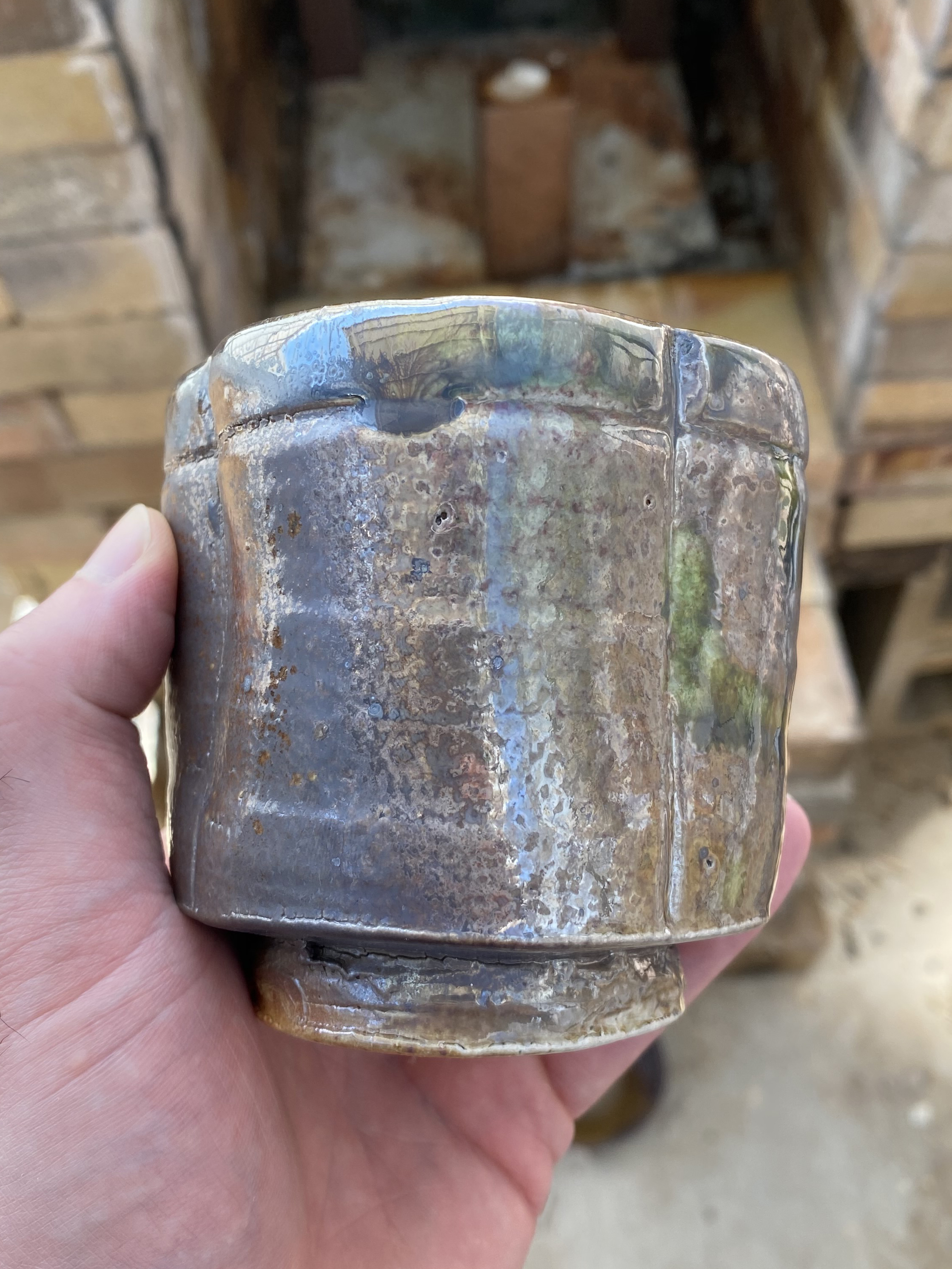 A ceramic cup with a slightly reflective, metallic-looking surface