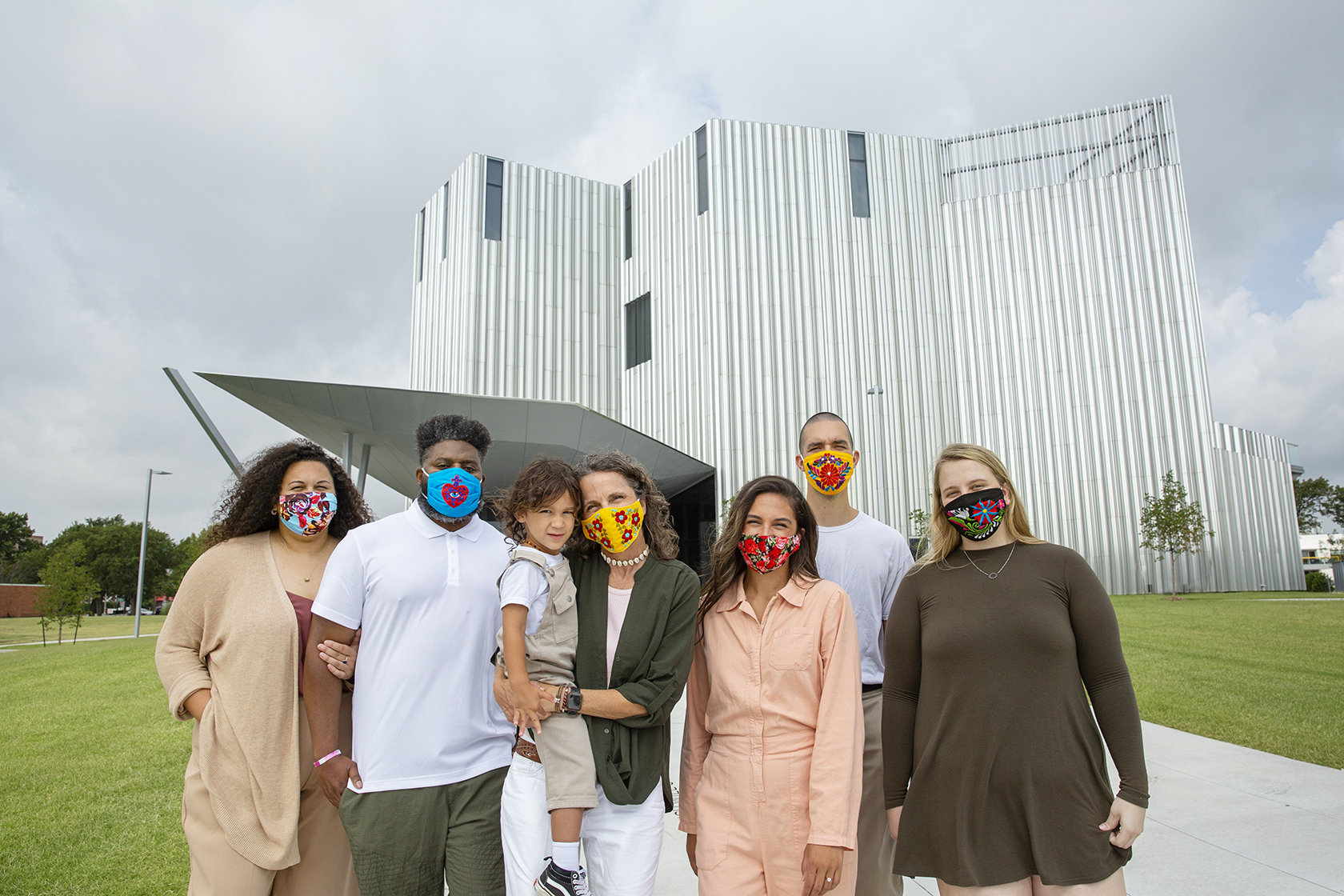 A masked family poses for a group photo in front of a contemporary metal building.
