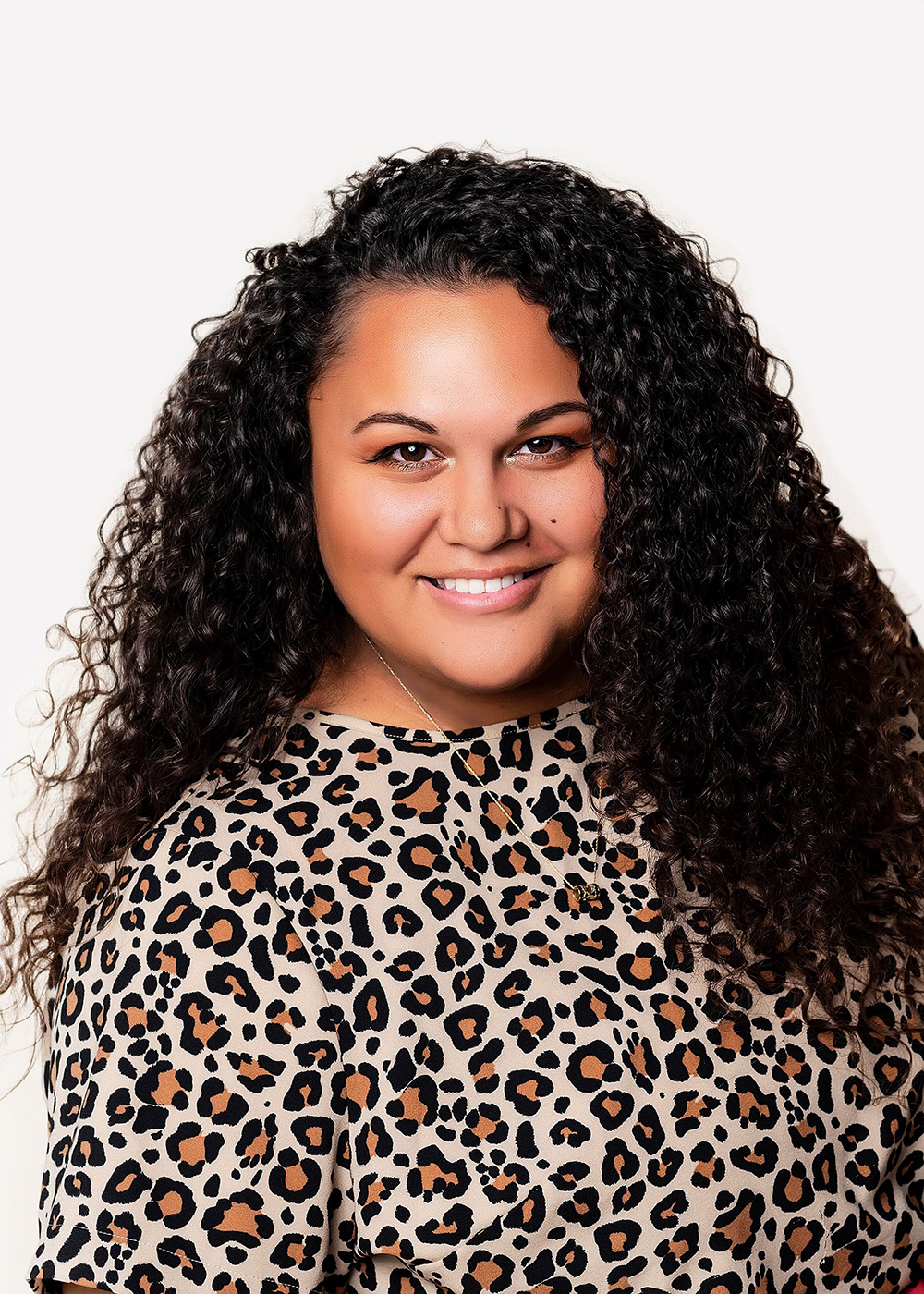 Smiling person with medium-colored skin and curly hair poses in a leopard print top