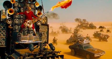 A guitarist shoots fire out of a guitar neck while speeding through the desert.