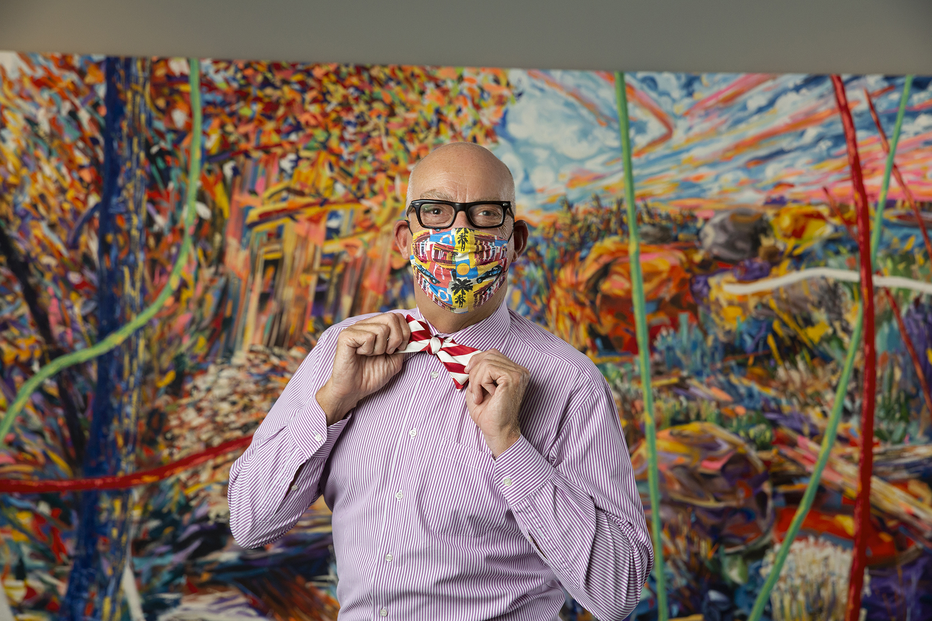 A masked figure in a bowtie poses in front of a vibrant, abstract landscape painting