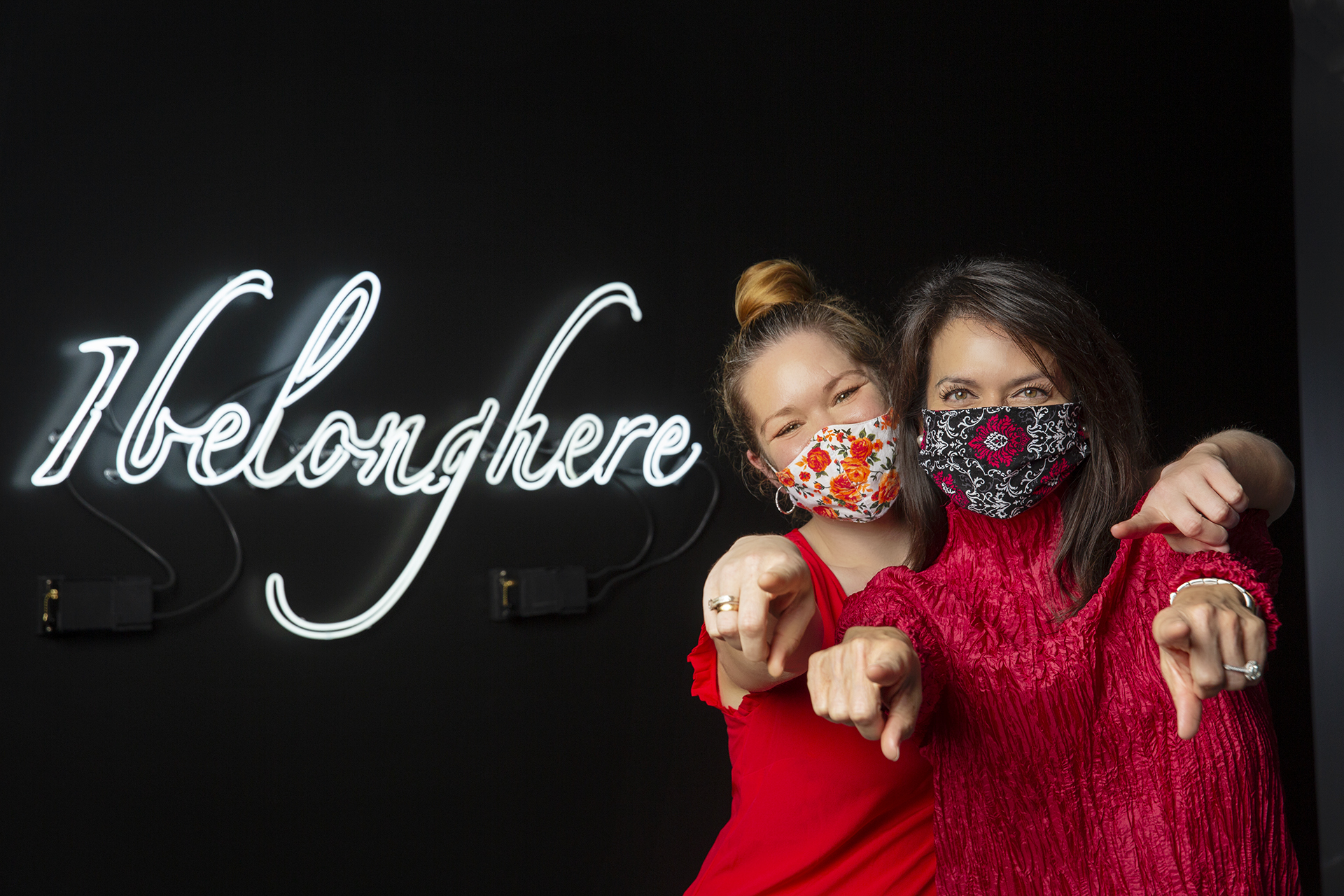 Masked figures pose in front of a light sculpture with text reading: I Belong Here