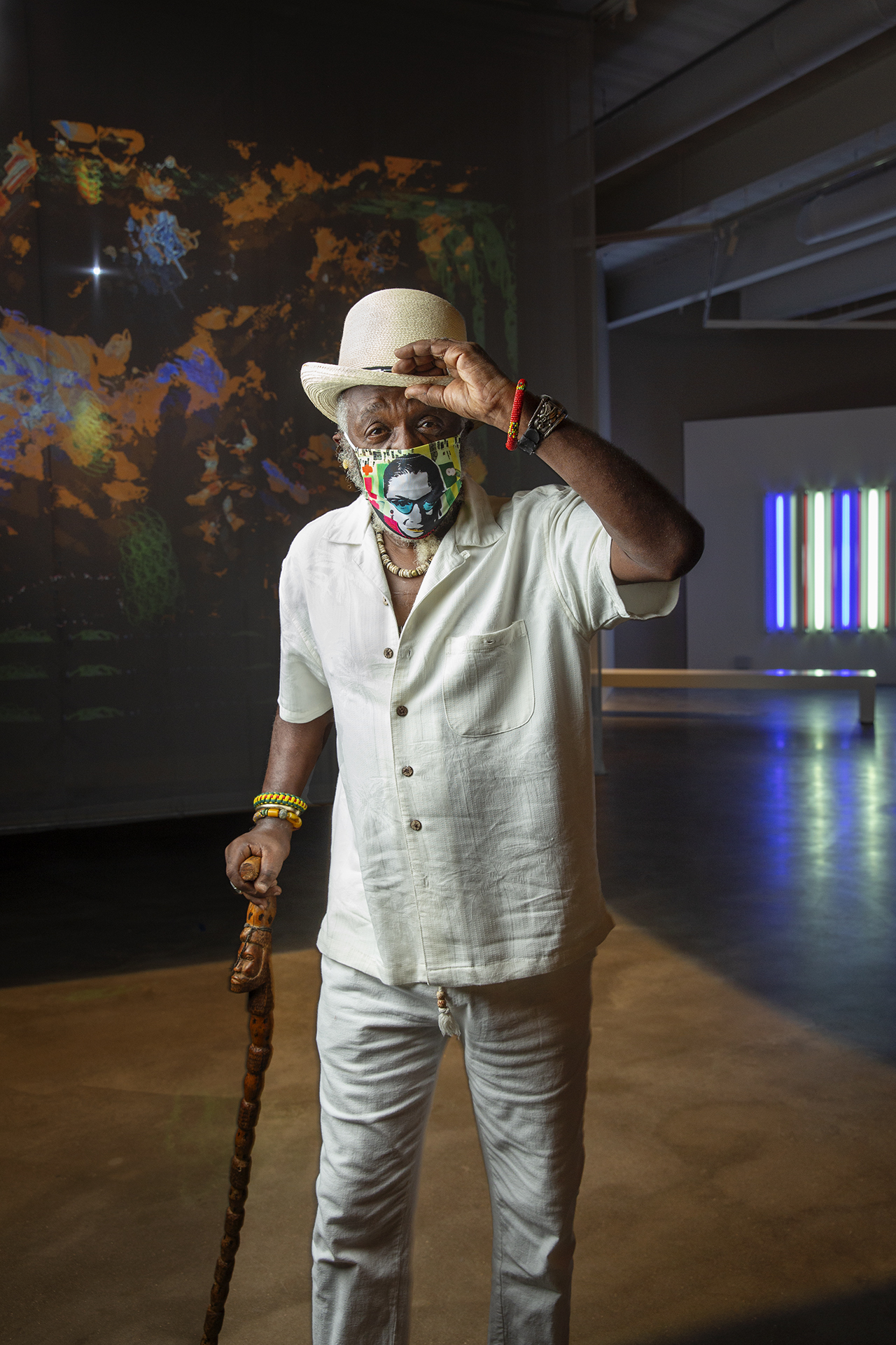 A figure with a hat and cane poses in front of an interactive light sculpture in a gallery space