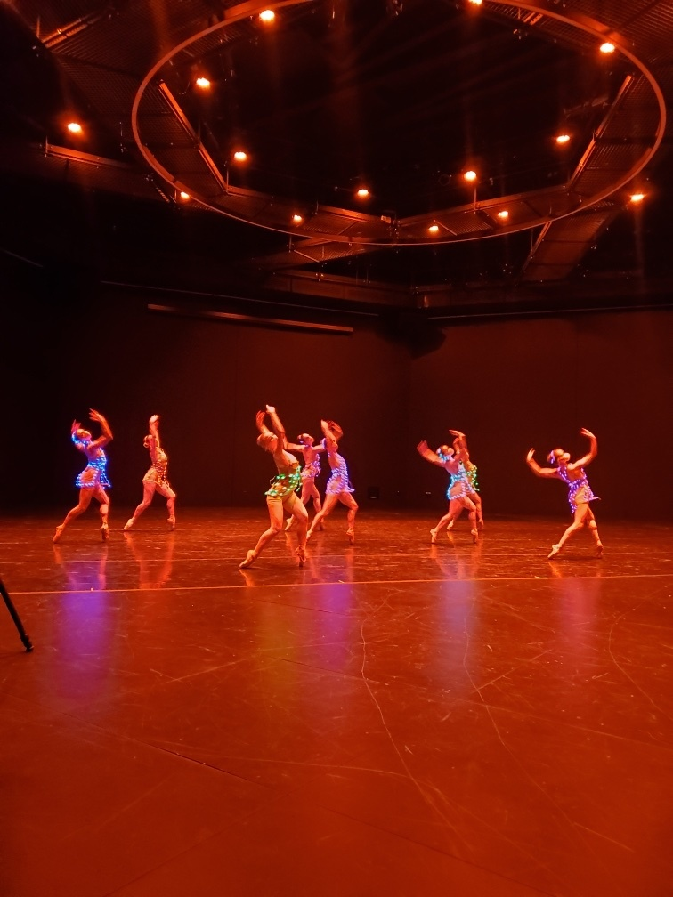 Dancers perform wearing illuminated leotards in a theater beneath a red light