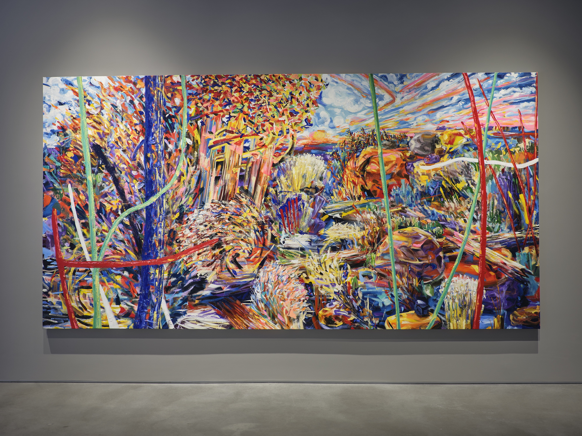 A photograph a large scale vibrant abstract landscape painting on view in an art gallery