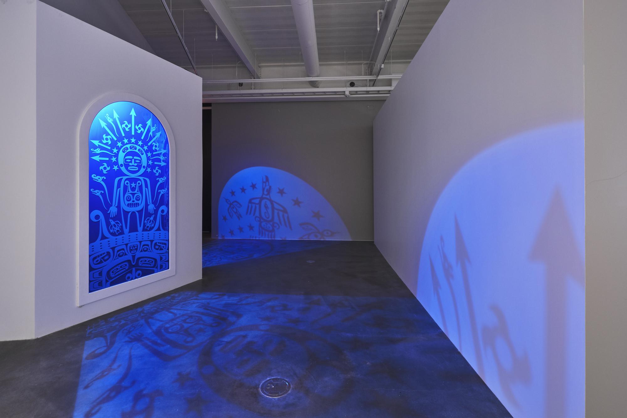 A photograph of a light sculpture emitting a blue light in an empty art gallery