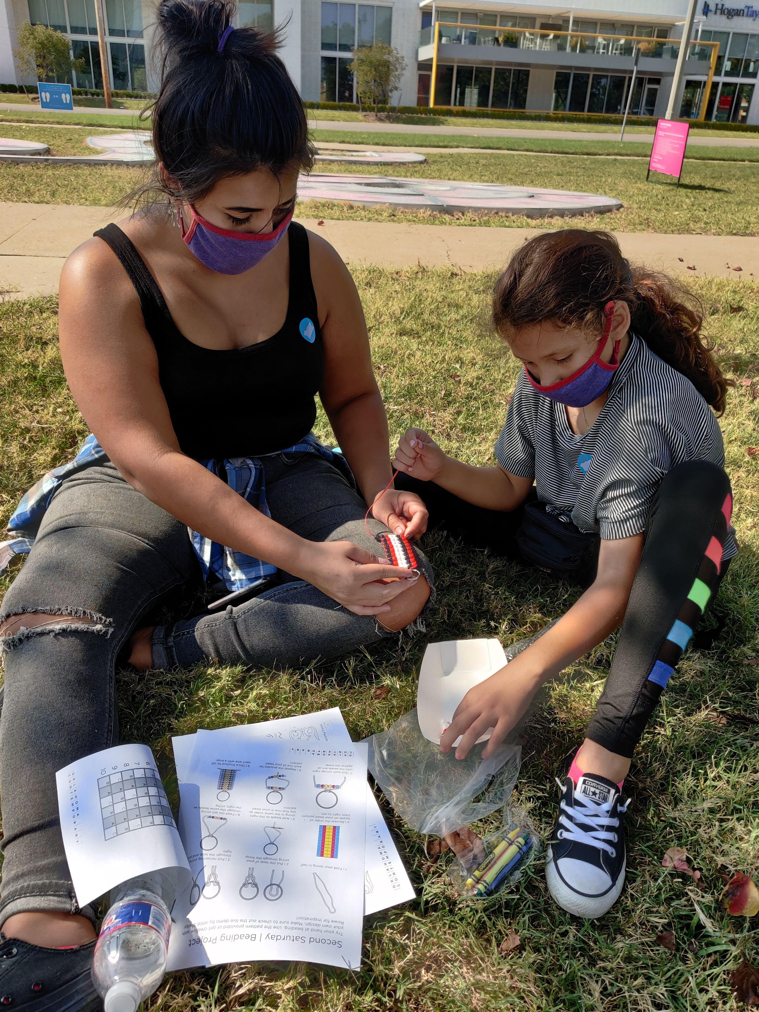 An adult and a child sit in the grass while working on an art project with beads