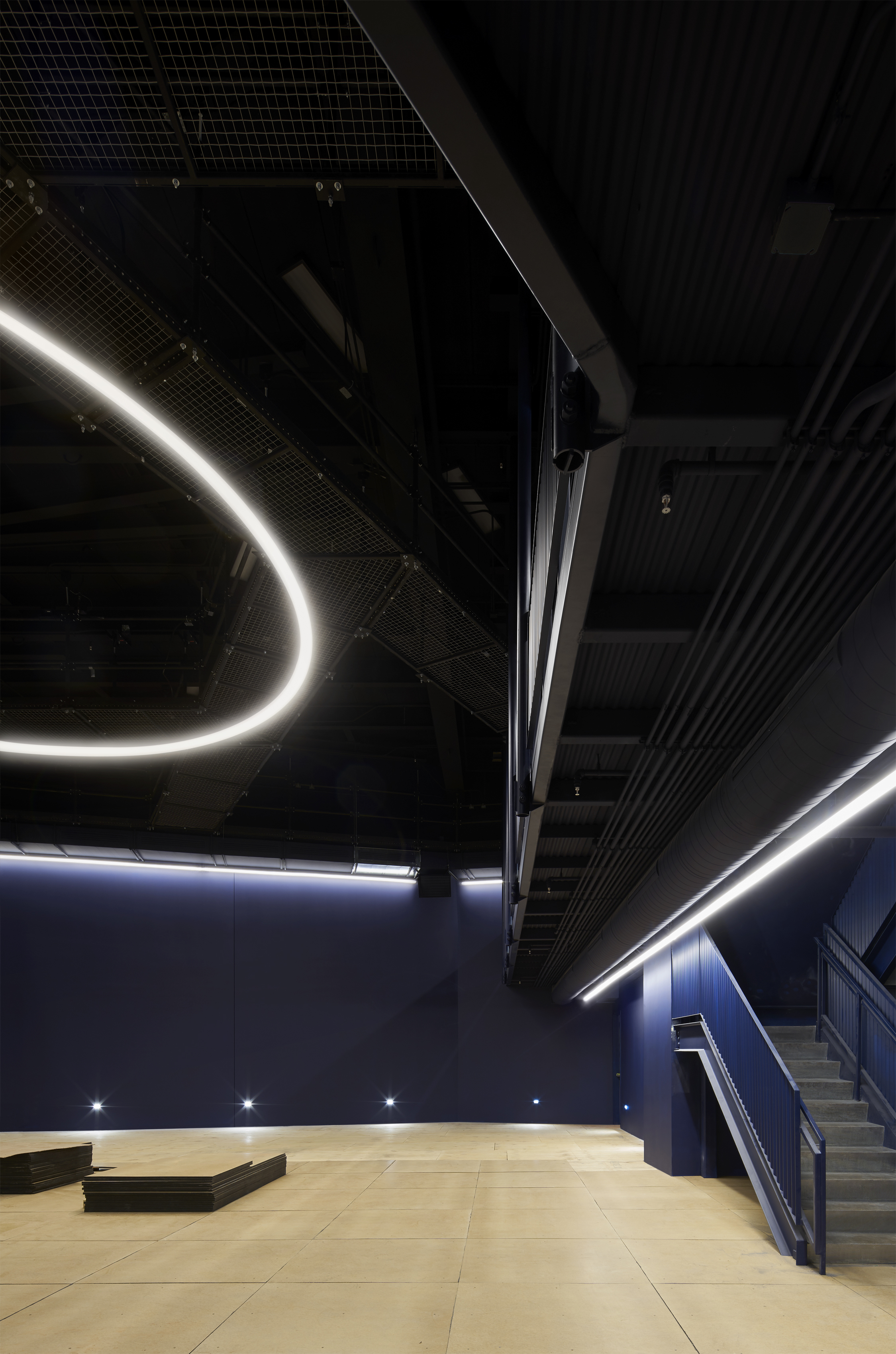 Section of a black-box theater, including a bare floor, LED lighting and navy walls