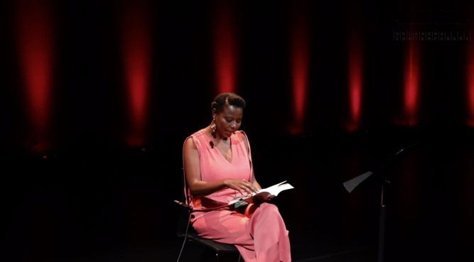 A figure in pink reads from a book in an elegantly lit theater space featuring predominantly red colors