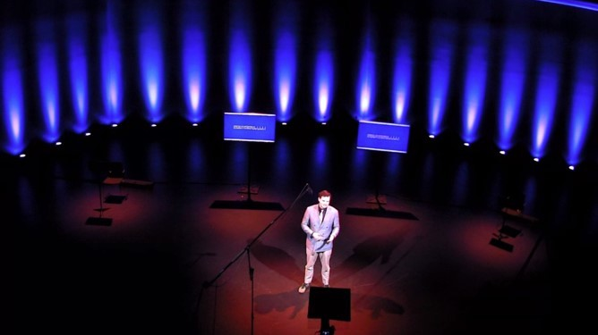 A figure presents in front of a camera in an elegantly lit theater space featuring predominantly blue colors