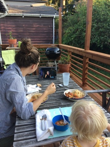 A family watches a person on a livestream outdoors while eating a meal