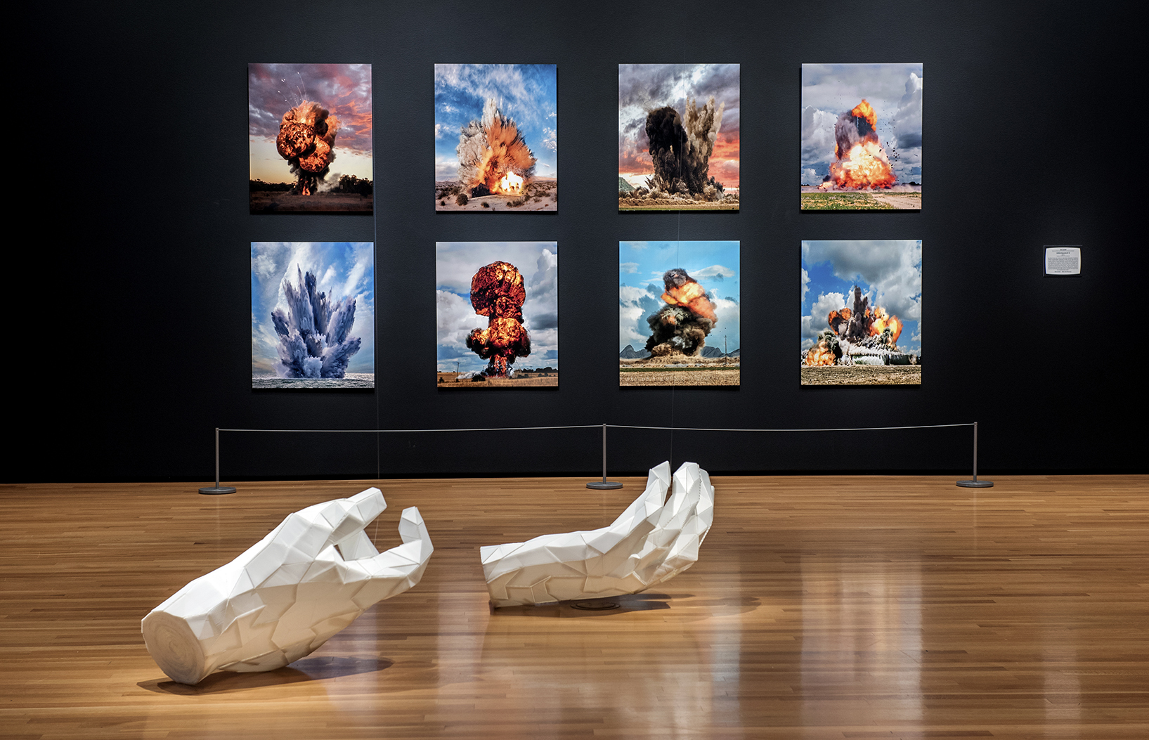 A pair of white, sculptural hands lay on a wood floor in a gallery with black walls featuring images of explosions.