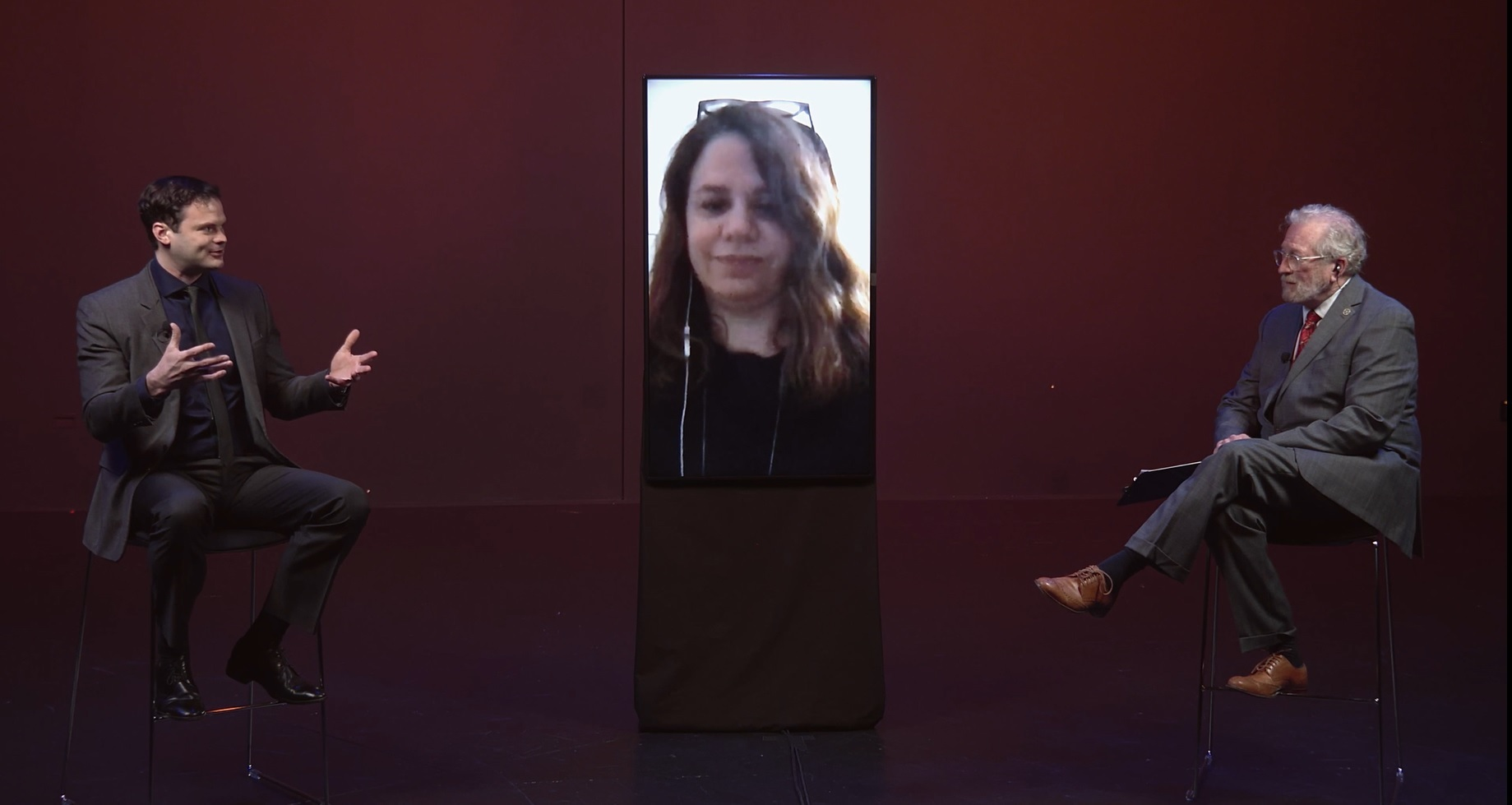 Three people sit on a panel discussion, two who are physically present in the theater space and another who is attending virtually on a large vertical screen
