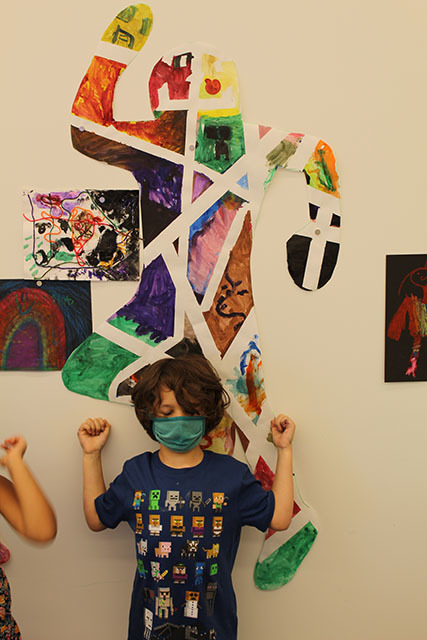 A child stands below a piece of art shaped like a person and decorated in sections