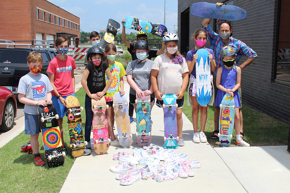 A group of children pose with skateboards and their instructor with a pile of shoes on the pavement