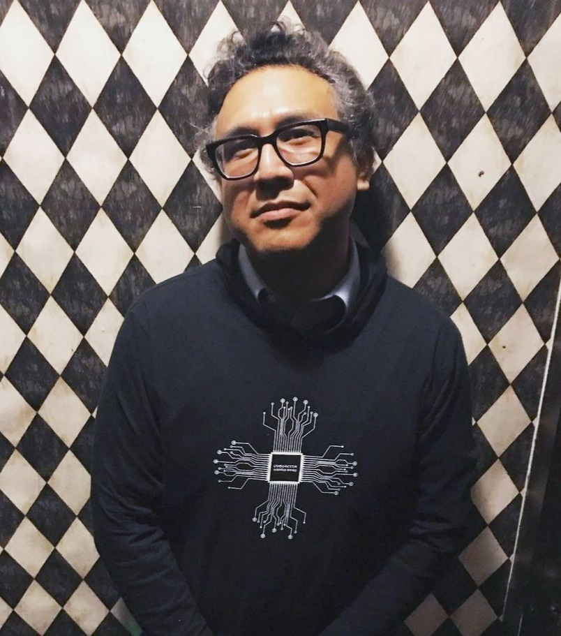 A person with dark features and chunky glasses poses in front of a black-and-white checkered wall
