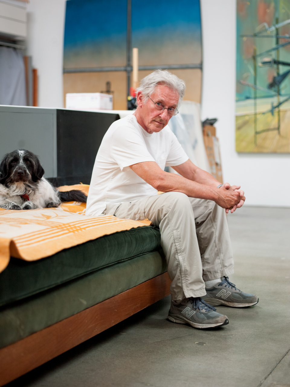 A figure in a white T-shirt and khaki pants and a dog sit on a couch in an art studiosits