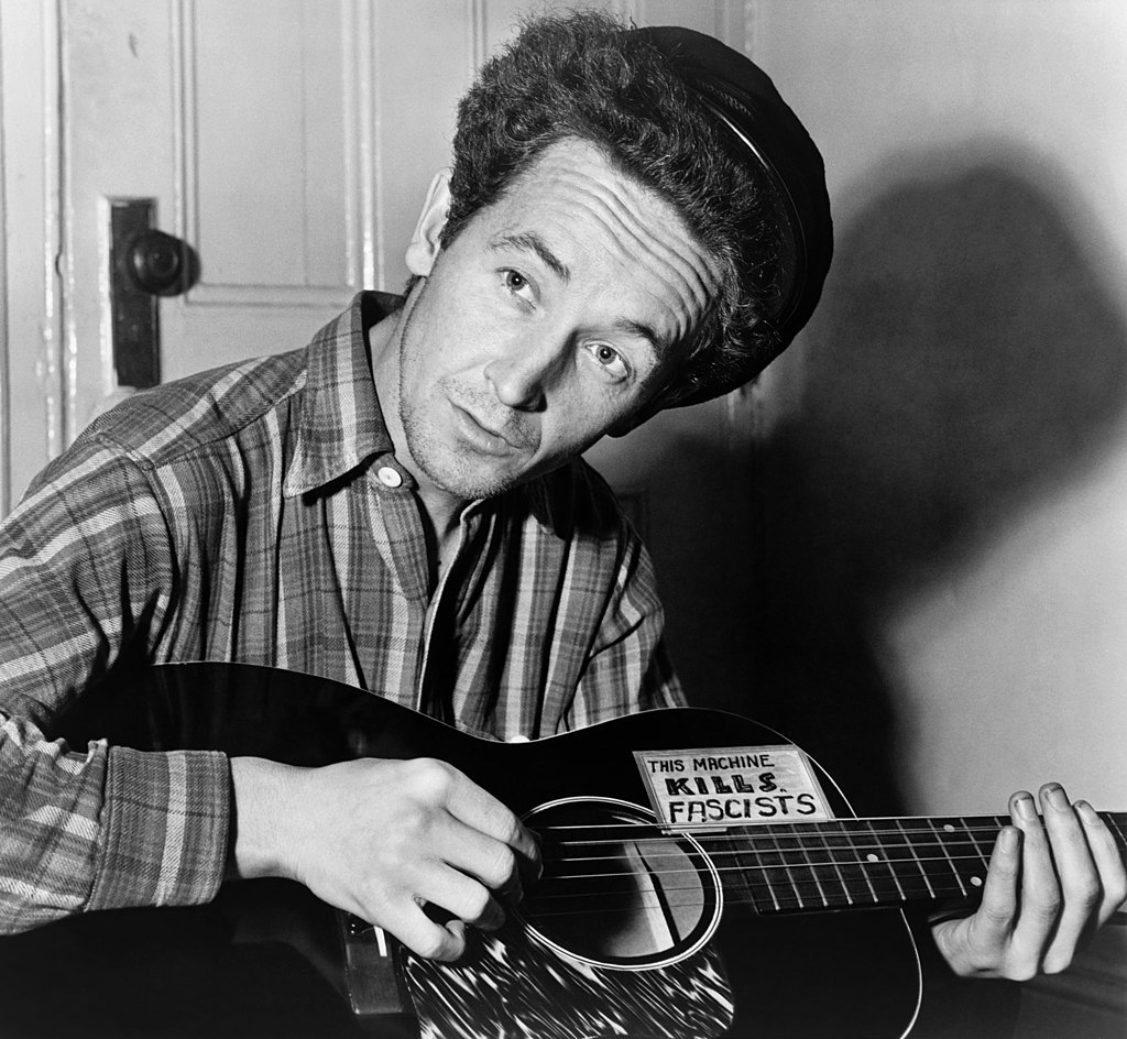 "A black and white photo depicts folk singer Woody Guthrie playing an acoustic guitar emblazoned with the phrase ""This machine kills fascists"""