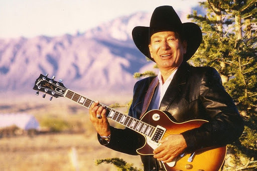 A person wearing a black cowboy hate poses with a sunburst electric guitar in the desert mountains