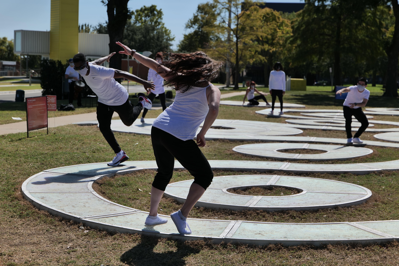 Dancers perform outdoors on an interactive light sculpture