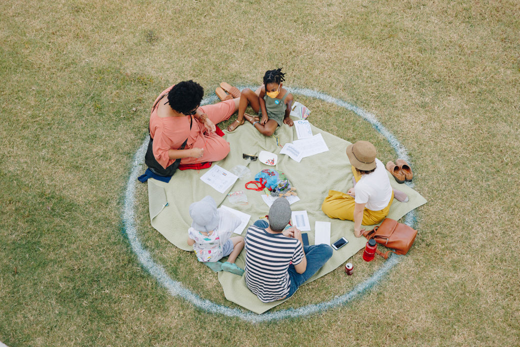 A group of four people sits on a blanket outdoors in a designated circle on a green lawn