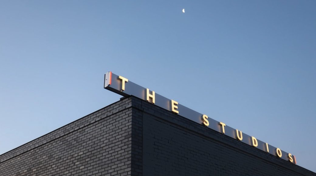 A detail shot of a building's upper corner at dusk, with a sign containing the following text: The Studios