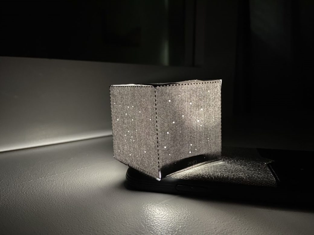A photo of a square, black box made of fabric, resembling a starry night sky and containing a small light source that faintly illuminates its surroundings