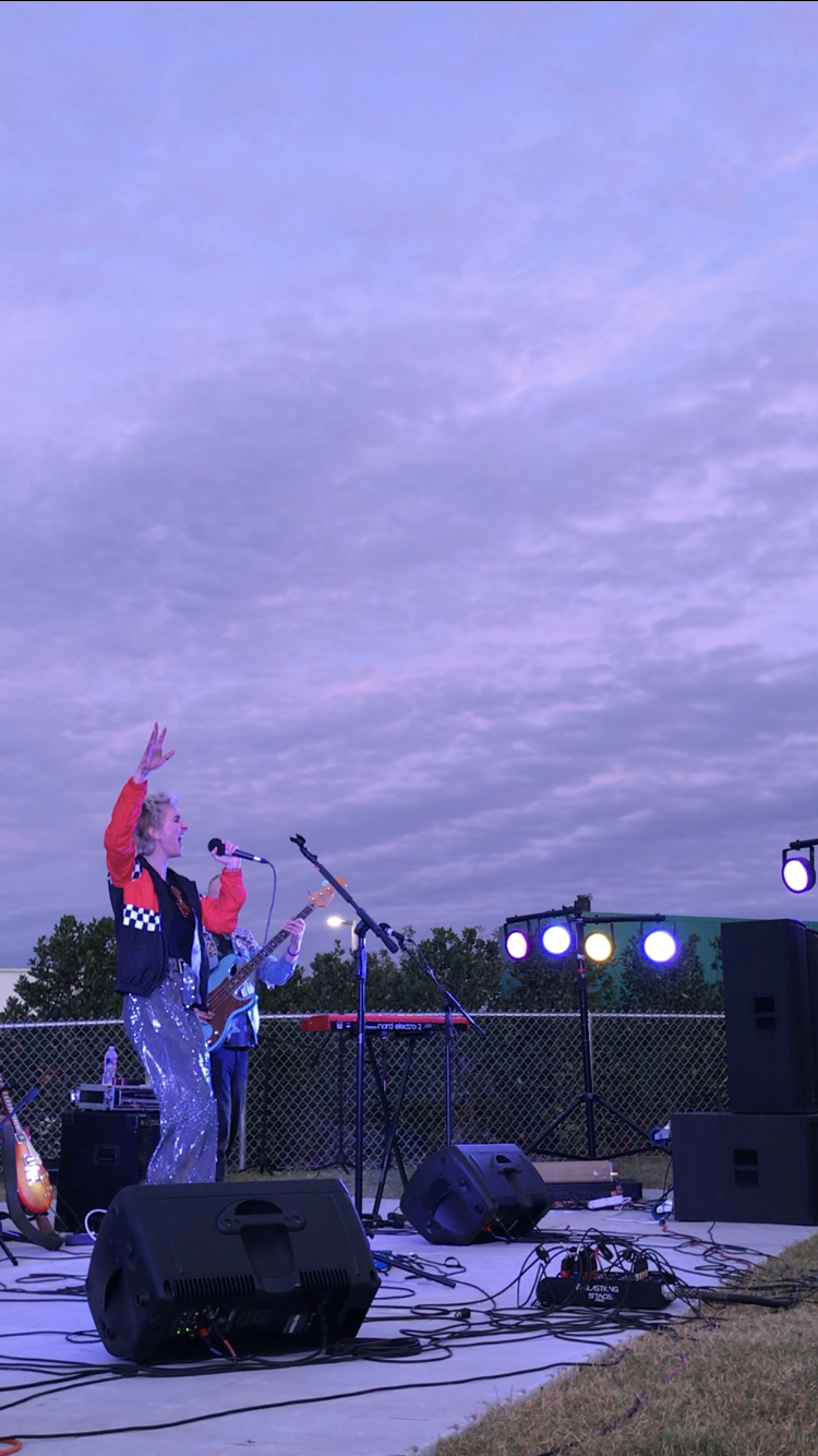 A performer sings into a microphone with a live band on an outdoor stage in the evening