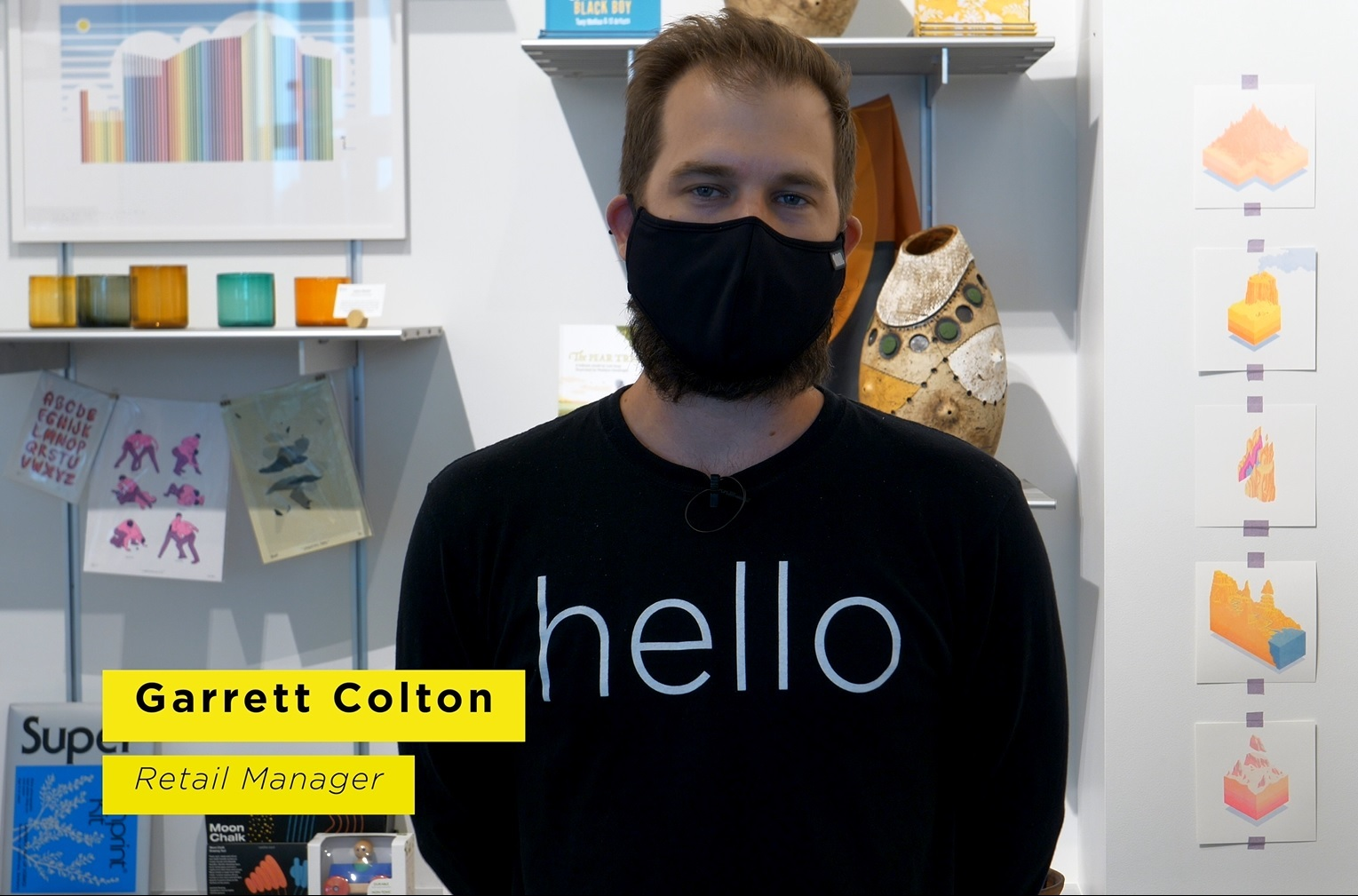 "A figure in a black mask, wearing a black shirt featuring the word ""hello,"" looks into the camera"