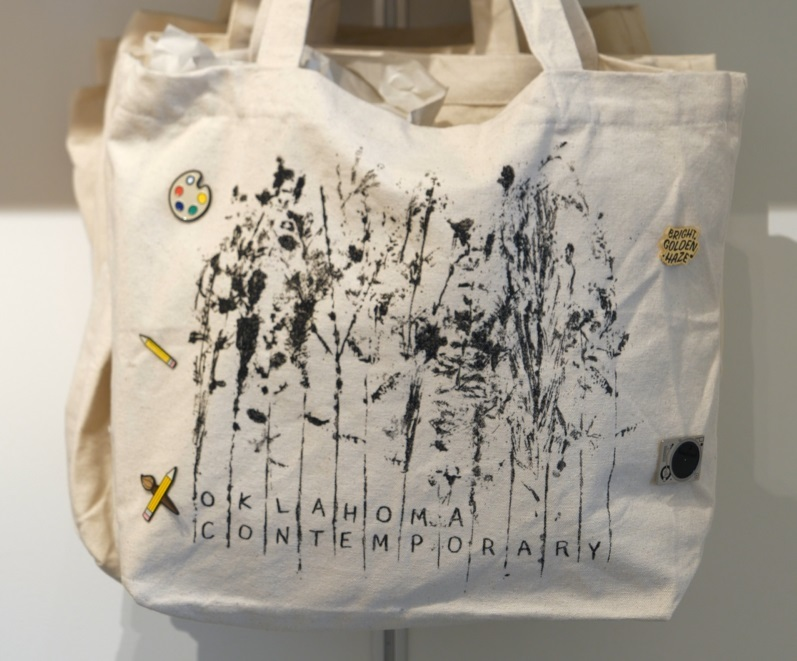 A white Oklahoma Contemporary tote bag featuring an abstract design of native plants and various colorful enamel pins
