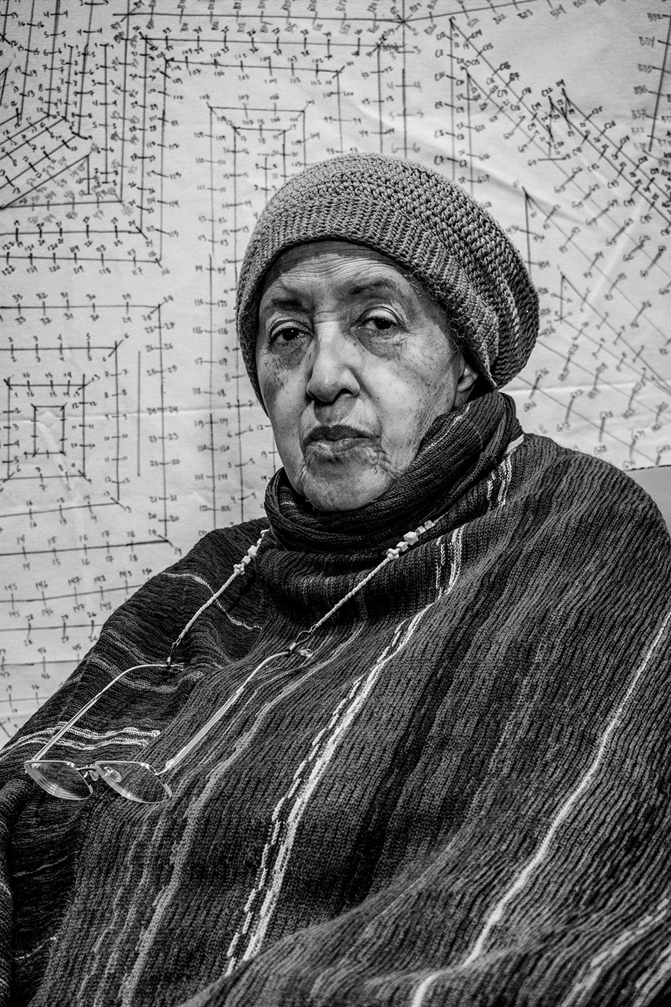 A black-and-white photo of a woman in a knitted cap and long shawl