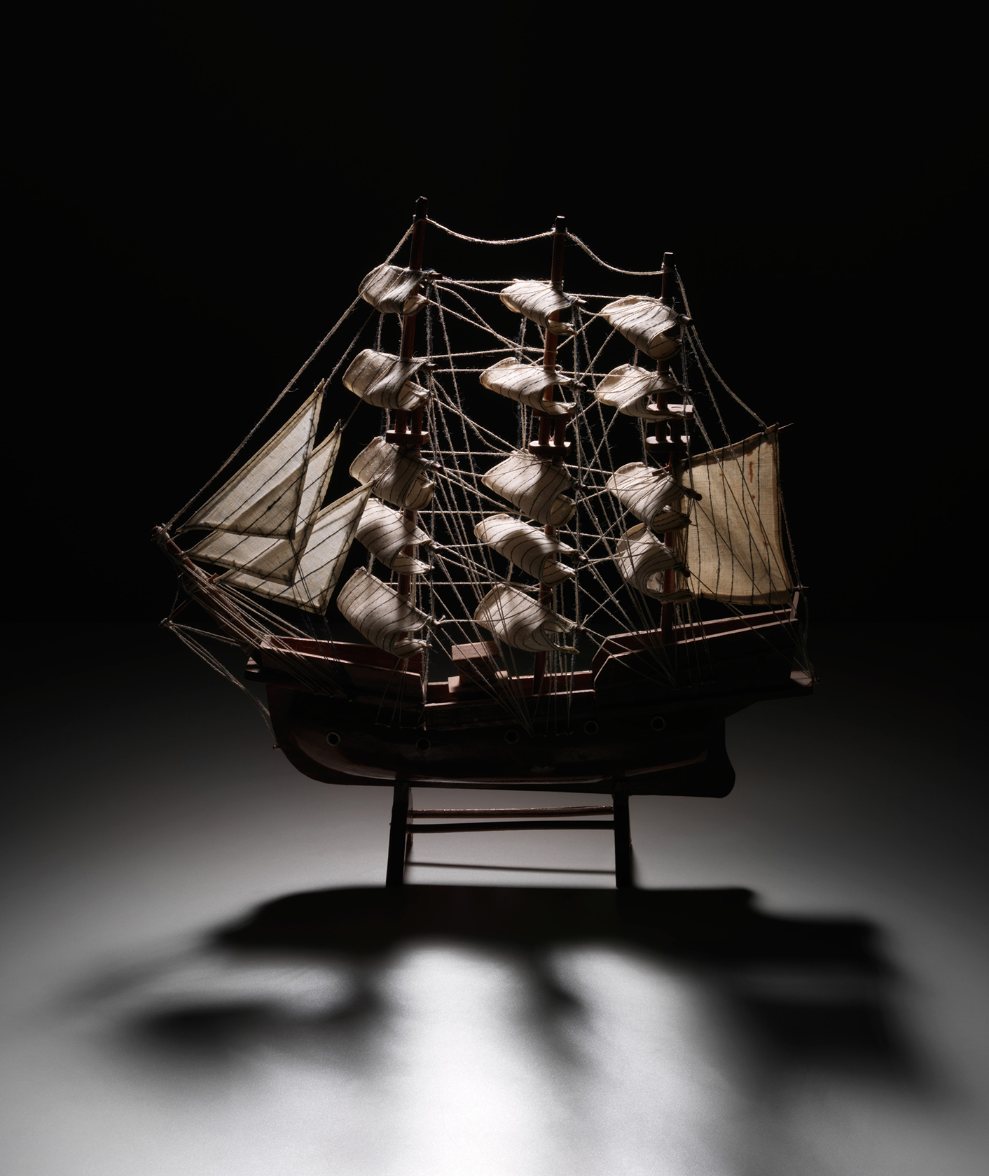 A model of an 1800s sailing ship sits on a neutral background
