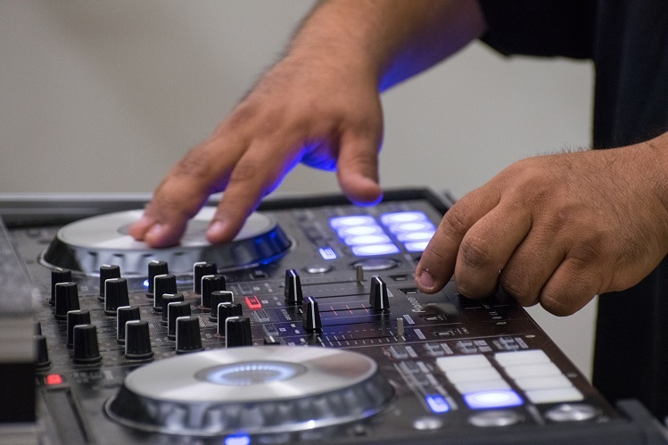A detail photo depicts hands manipulating a DJ sound board