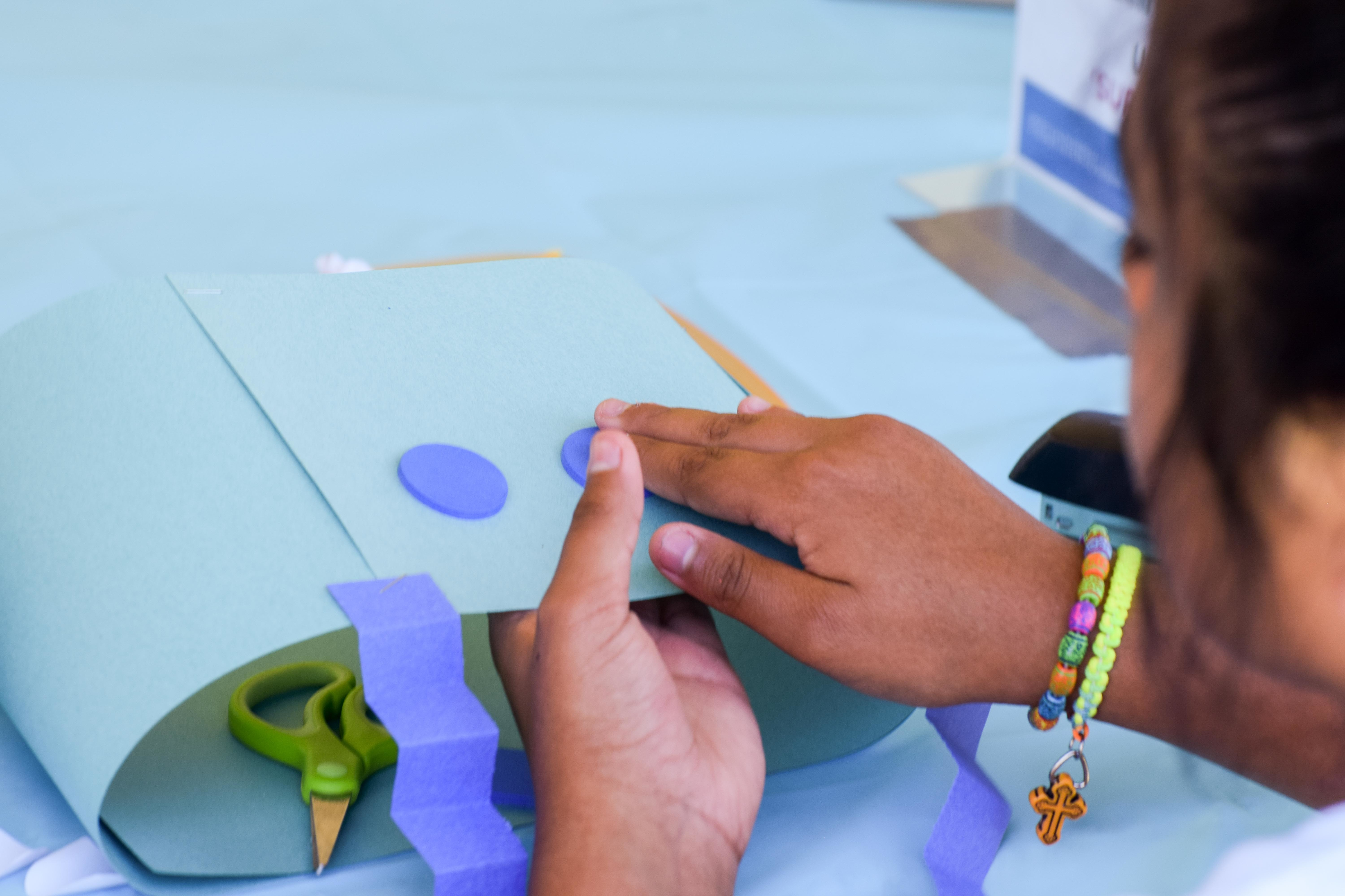 A detail photo depicts the hands of a child working on an art project using scissors and construction paper