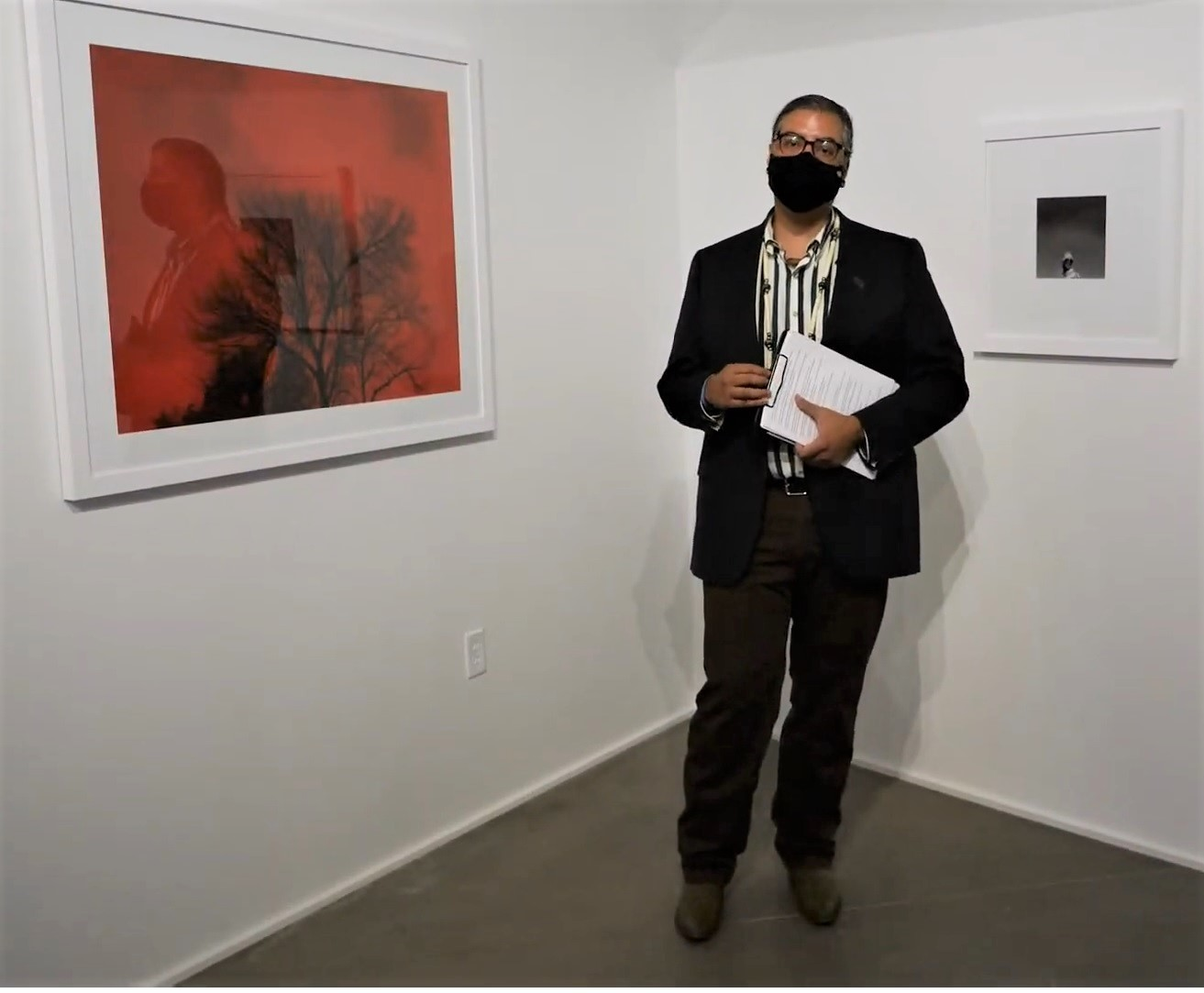 A masked figure holding a clipboard speaks in front of photographs hanging in an art gallery